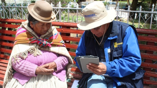 Enlargement: A Peruvian woman and a project member of Climandes sit on a bench while they work together to complete the survey on their needs.