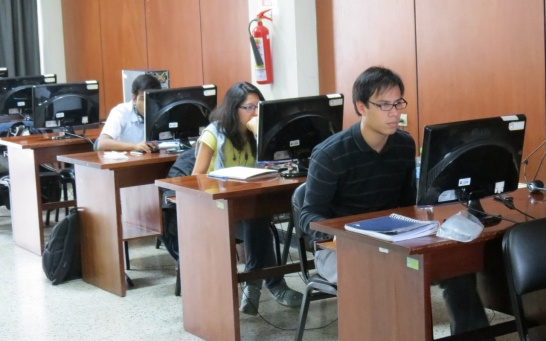 Enlargement: Students sit in a class room and work on e-learning modules.