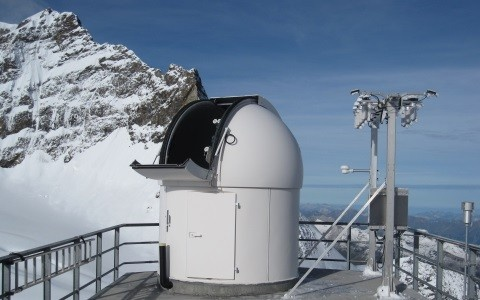 Photography of the SACRaM station showing an astronomical cupola protecting radiation instruments on top of the Sphinx building at Jungfraujoch. A 3-meter tall measurement bench is on the right of the picture supporting radiometers measuring UV, global solar and thermal infrared irradiance.