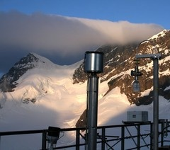Enlargement: The air intakes are arranged on an open-air terrace. The instrument seen in the centre of the image consists of a tube fixed to the vertical pole and topped with a metal container across which the air is passed. Mountains and glaciers can be seen in the background.